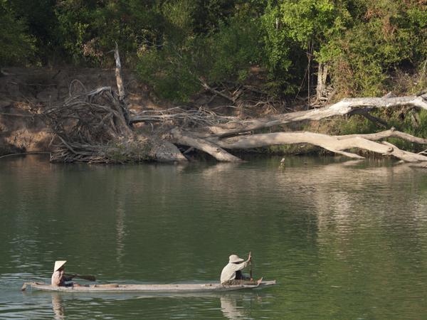 メコン川を下る村人。船は細長いものが多い。流れはほとんどない。