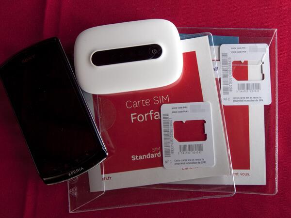SIMカードを装填されたスマートフォンとWi-Fiルーター。