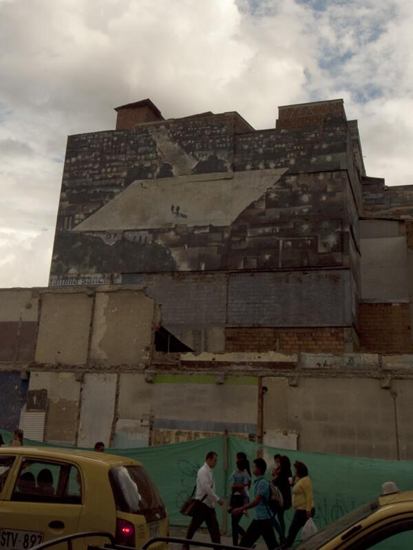 サン・アントニオ駅の壁画。ビルの壁いっぱいいっぱいに、密集した貧しい家々の真ん中にグランドが、描かれています。