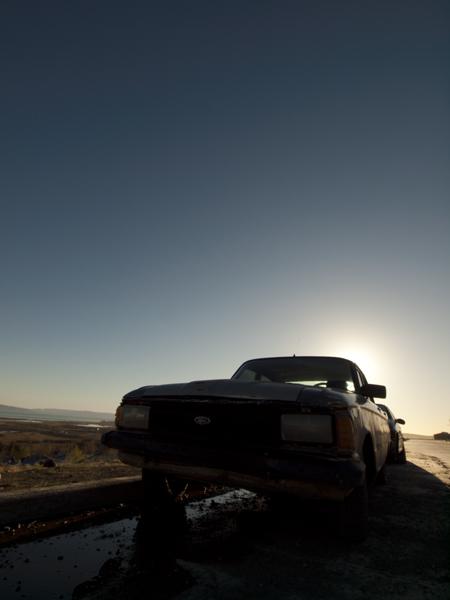 捨て置かれた車に朝陽。